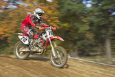 Motocross racer in red id riding — Stock Photo