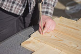 Man is bolting  screwed into a wooden board.  — Stock Photo
