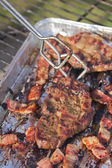 Turning grilled steak and bacon — ストック写真