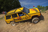 Yellow offroad car is hitting a steep hill — ストック写真