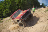 Red offroad car is in great lateral tilt — ストック写真