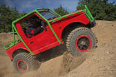 Small red off road car is hitting a steep hill — Foto Stock