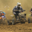 Group Quad motorbike racers in the dust shrouded — Stock Photo #9419145