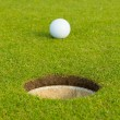 Golf ball in front of the hole, focus on the hole — Stock Photo