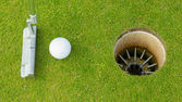Golf ball and tee on green cours — Stock Photo
