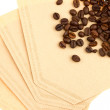 Coffee beans on a coffee filter (white background) — Stock Photo