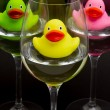Green, yellow and pink rubber ducks in wineglasses - Stock Photo