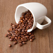 Coffee cup and spilled coffee beans — Stock Photo