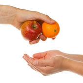 Giving an apple and an orange — Stock Photo