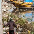 Woman collecting garbage in a harbour in Vietnam — Stock Photo
