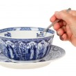 Old lady (hand) holding a spoon in an antique Dutch soup bowl in — Stock Photo #14799831