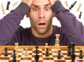 Chessboard with desperate man thinking about chess strategy, iso — Stock Photo