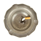 Burning cigarette in an old tin ashtray — Stock Photo