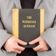 Stock Photo: Womholding marriage almanac
