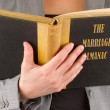 Stock Photo: Womreading marriage almanac