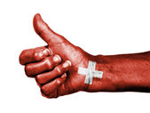 Old woman with arthritis giving the thumbs up sign, wrapped in f — Stock Photo