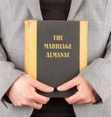 Woman holding a marriage almanac — Stock Photo
