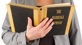 Woman reading a marriage almanac — Stock Photo