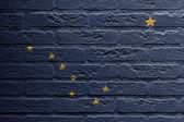 Pared de ladrillo con una pintura de una bandera, alaska — Foto de Stock