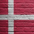 Brick wall with a painting of a flag, Denmark - Stockfoto