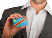 Businessman is holding a business card, The Democratic Republic — Stock Photo