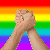 Man and woman in arm wrestlin, rainbow flag pattern — Stock Photo