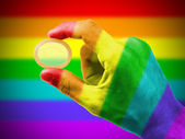 Male giving a condom, rainbow flag pattern — Stock Photo