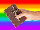 Old hand (woman) holding a very old bible, rainbow flag — Stock Photo