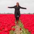 Woman standing in a field of tulips — Stock Photo