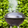 Old black barbecue being used — Stock Photo