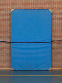 Large blue mat strapped to a brick wall — Stock Photo