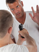 Scared man being threatened by a man with a handgun — Stock Photo