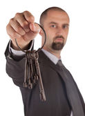 Man in suit giving old keys to a house — Stock Photo