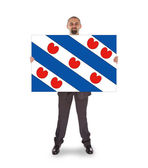 Smiling businessman holding a big card, flag of the dutch provin — Stok fotoğraf