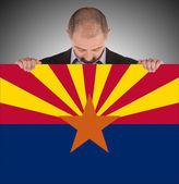 Empresario sonriente sosteniendo una tarjeta grande, bandera de arizona — Foto de Stock