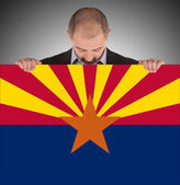 Smiling businessman holding a big card, flag of Arizona — Stock Photo