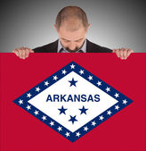 Smiling businessman holding a big card, flag of Arkansas — Stok fotoğraf