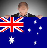 Smiling businessman holding a big card, flag of Australia — Stok fotoğraf
