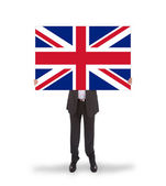 Smiling businessman holding a big card, flag of the United Kingd — Stock Photo