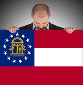 Smiling businessman holding a big card, flag of Georgia — Foto de Stock
