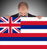 Smiling businessman holding a big card, flag of Hawaii — Stock Photo