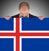 Smiling businessman holding a big card, flag of Iceland — Stok fotoğraf