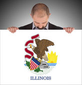 Smiling businessman holding a big card, flag of Illinois — Stok fotoğraf