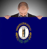 Büyük bir kart, kentucky bayrağı tutarak gülümseyen iş adamı — Stok fotoğraf