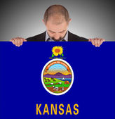 Smiling businessman holding a big card, flag of Kansas — Stok fotoğraf