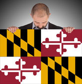 Smiling businessman holding a big card, flag of Maryland — Stock Photo