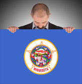 Smiling businessman holding a big card, flag of Minnesota — Stock Photo