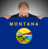 Smiling businessman holding a big card, flag of Montana — Photo
