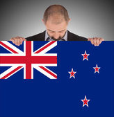 Smiling businessman holding a big card, flag of New Zealand — Stock Photo