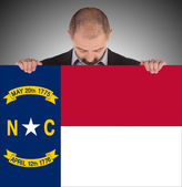 Smiling businessman holding a big card, flag of North Carolina — Stock Photo
